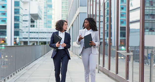 Photo of two business women walking and talking